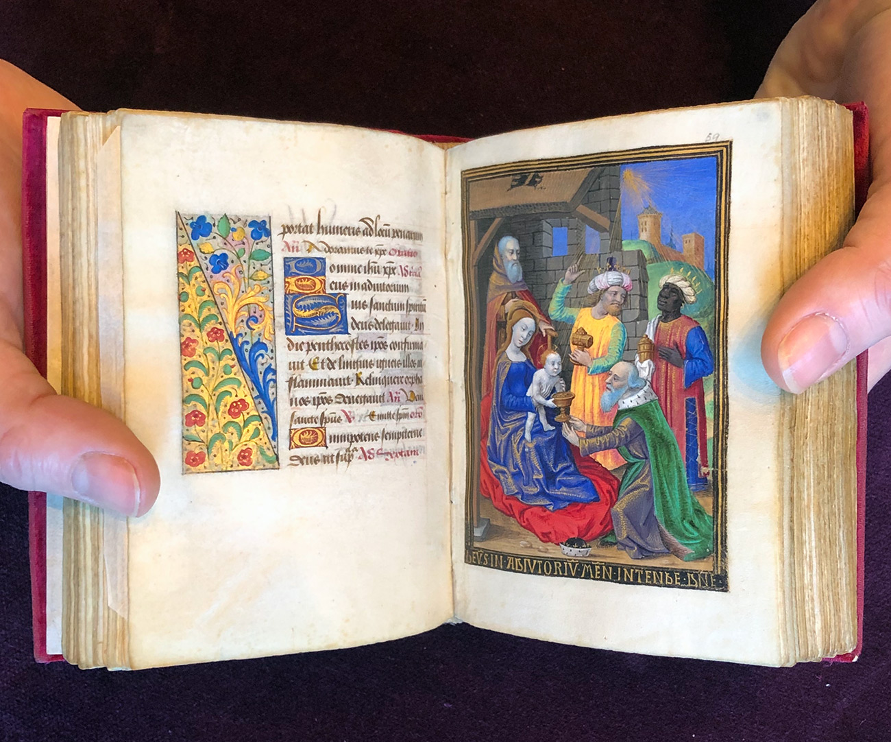 Close-up of two hands holding a tiny medieval manuscript open to a brightly painted page showing the adoration of the magi, one of whom has dark skin