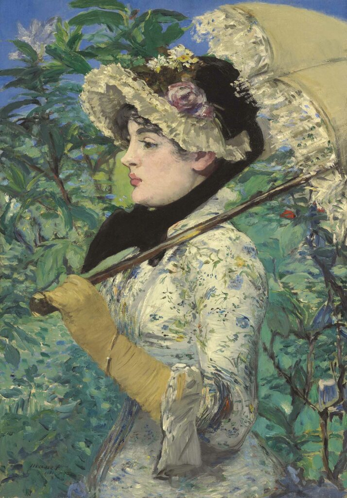 Side view of a woman in a white flowered dress, tan gloves, and frilly hat, holding a tan and lace parasol, with a greenery-filled background.