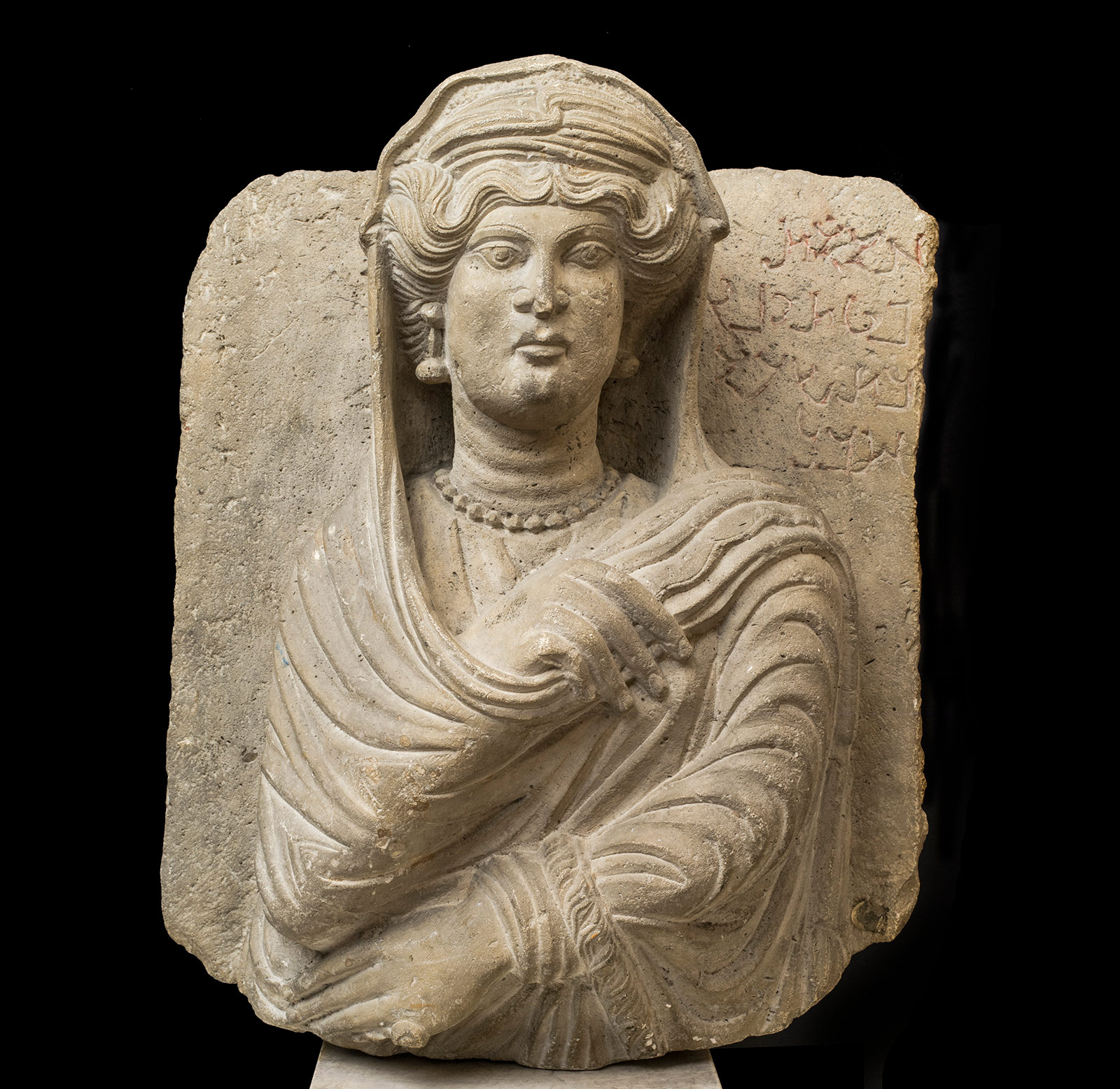 Limestone bust of a woman in a headdress holding her right hand to her shoulder