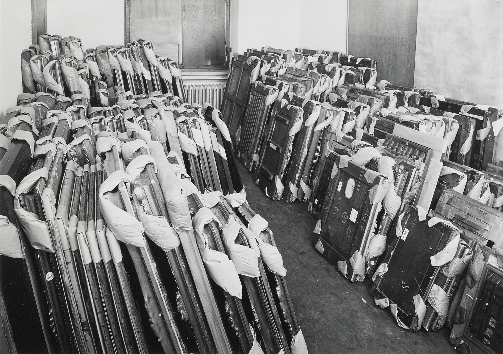 A black and white photograph of approximately 100 framed objects stacked against the walls of an otherwise empty room.