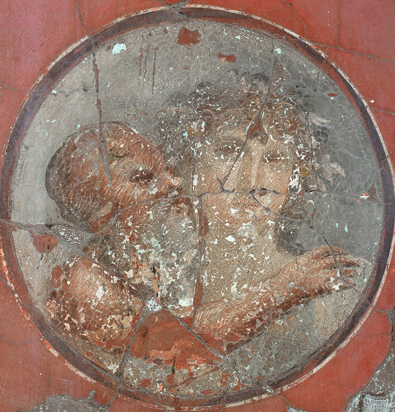 A round wall painting depicts a bearded man embracing a young woman.