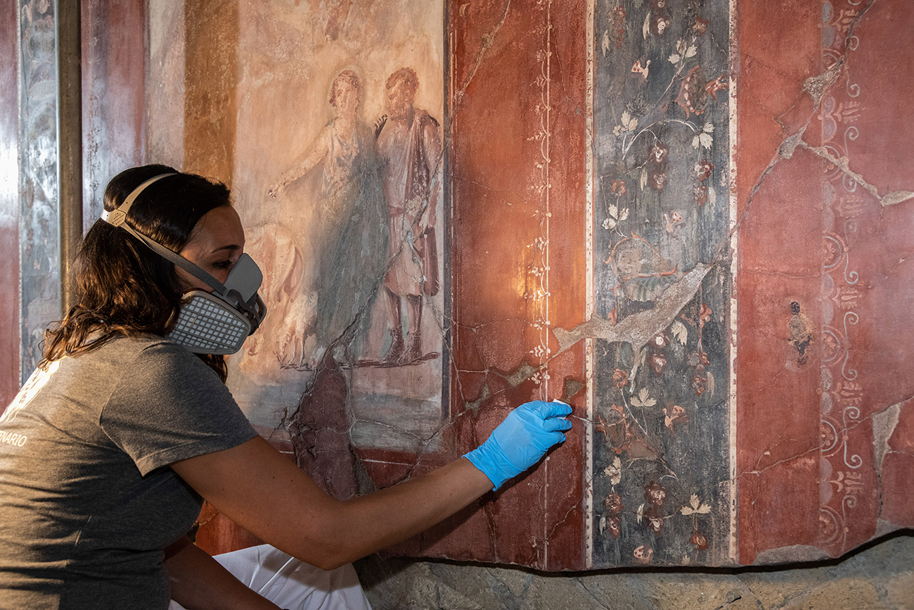 A conservator wearing a face mask treats a wall painting in the tablinum.