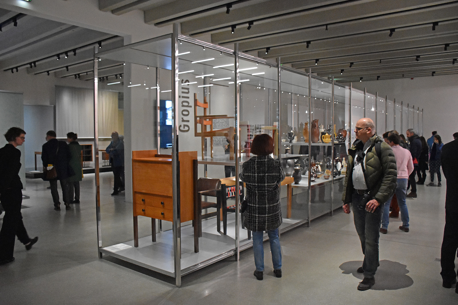 A large room with floor to ceiling glass cases in the middle, containing wooden furniture and vases. People in jackets walk around in front of and behind the cases.