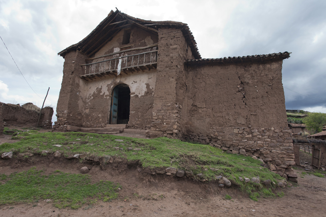 Close-up view of a church made of earth and bricks. Bricks are exposed, and cracks in the wall are visible.