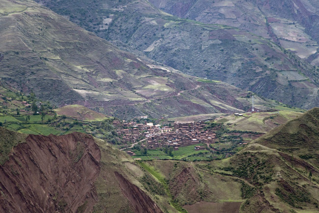 Aerial view of a village in the Andes, with a cluster of buildings built of earth and surrounded by farming fields