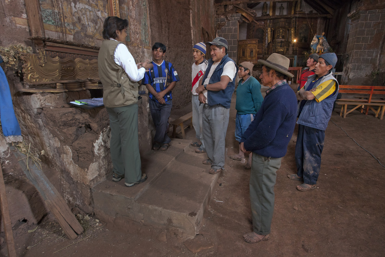 Inside an adobe church, a woman in work clothes speaks to a group of seven Peruvian men, who listen attentively.