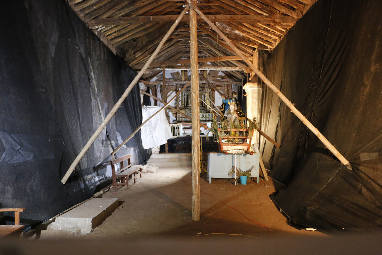 Interior view of a wood-framed structure with large black plastic sheets protecting the walls at left and right