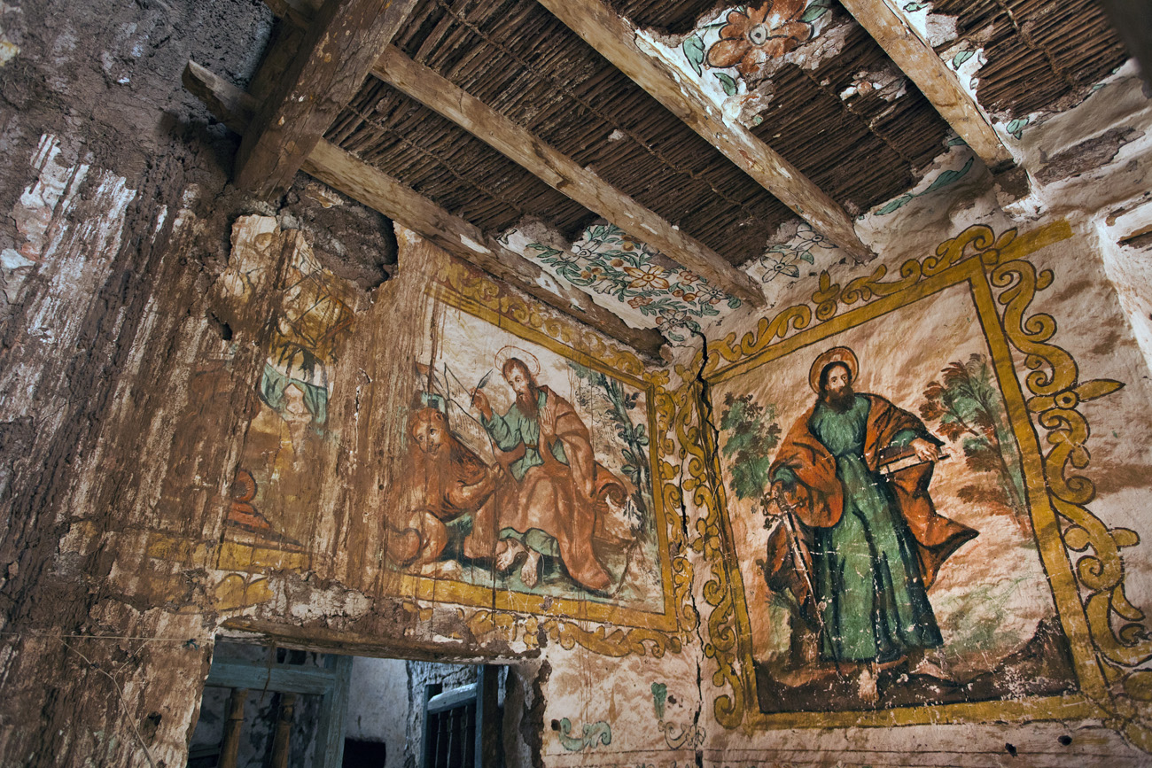 Interior of a church made of wood and earth showing wall paintings of two saints. The walls are water-damaged and show cracks and wear