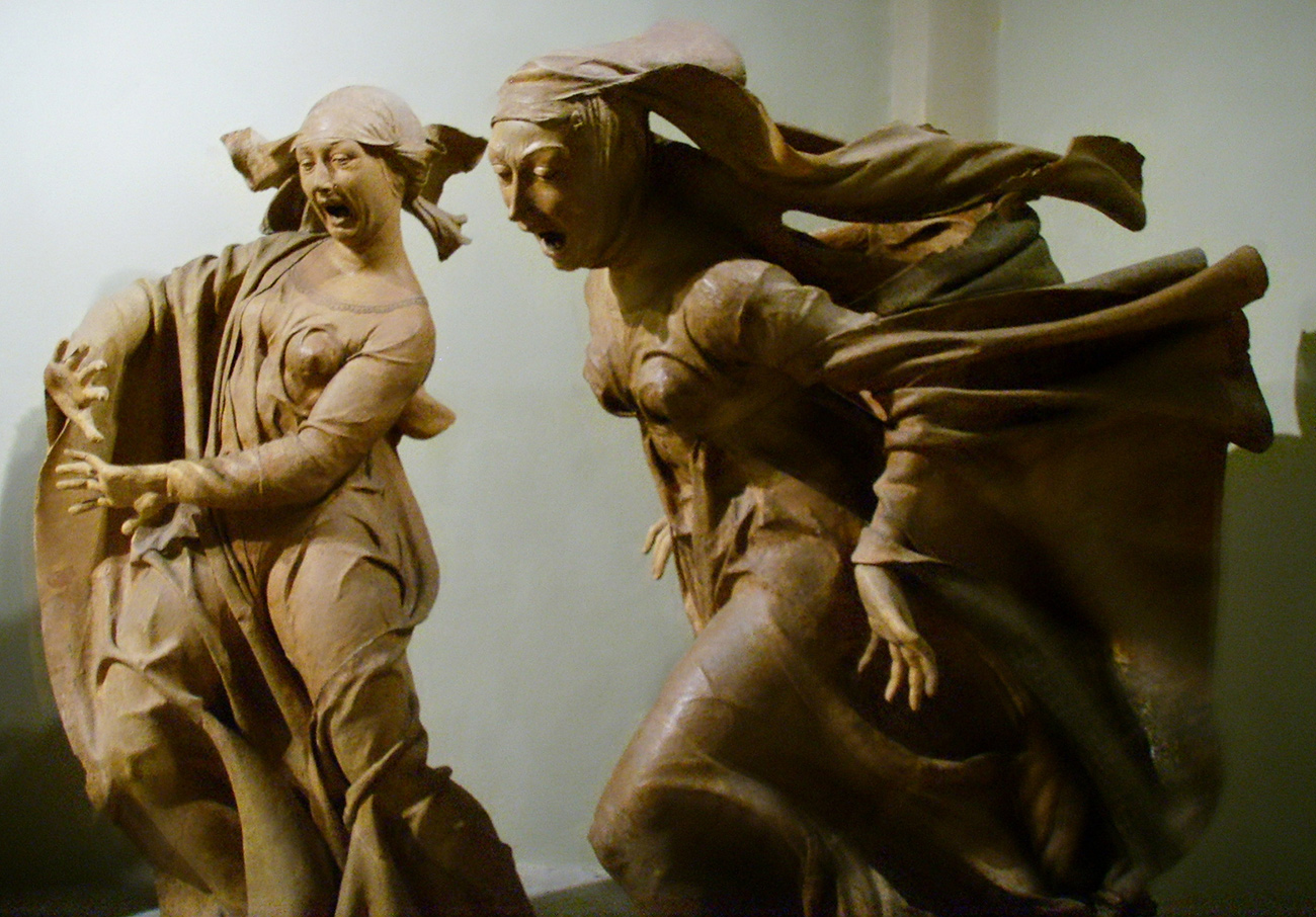 Sculpture of two women in robes and headresses, mouths wide in expressions of anguish.