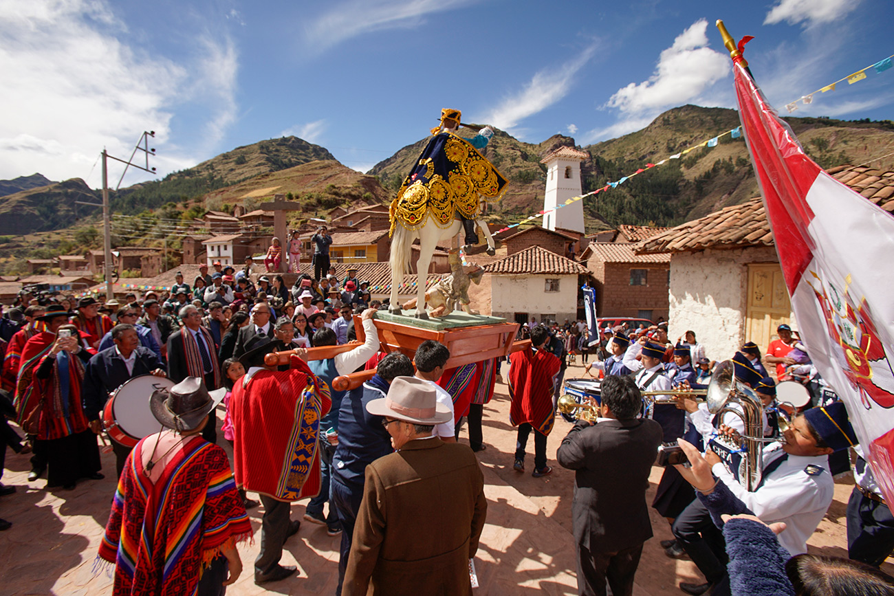 A procession in the streets of Kunotamo, an Andean village in Peru. People carry a sculpture of the Saint Santiago.