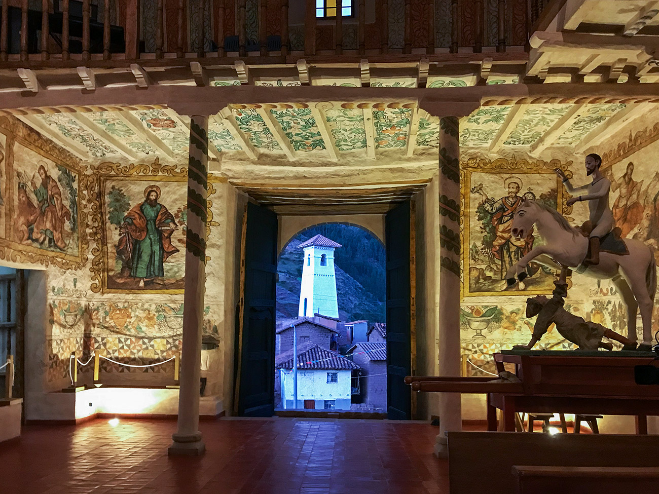 The interior of the church showing wall paintings and the bell tower outside at dusk.