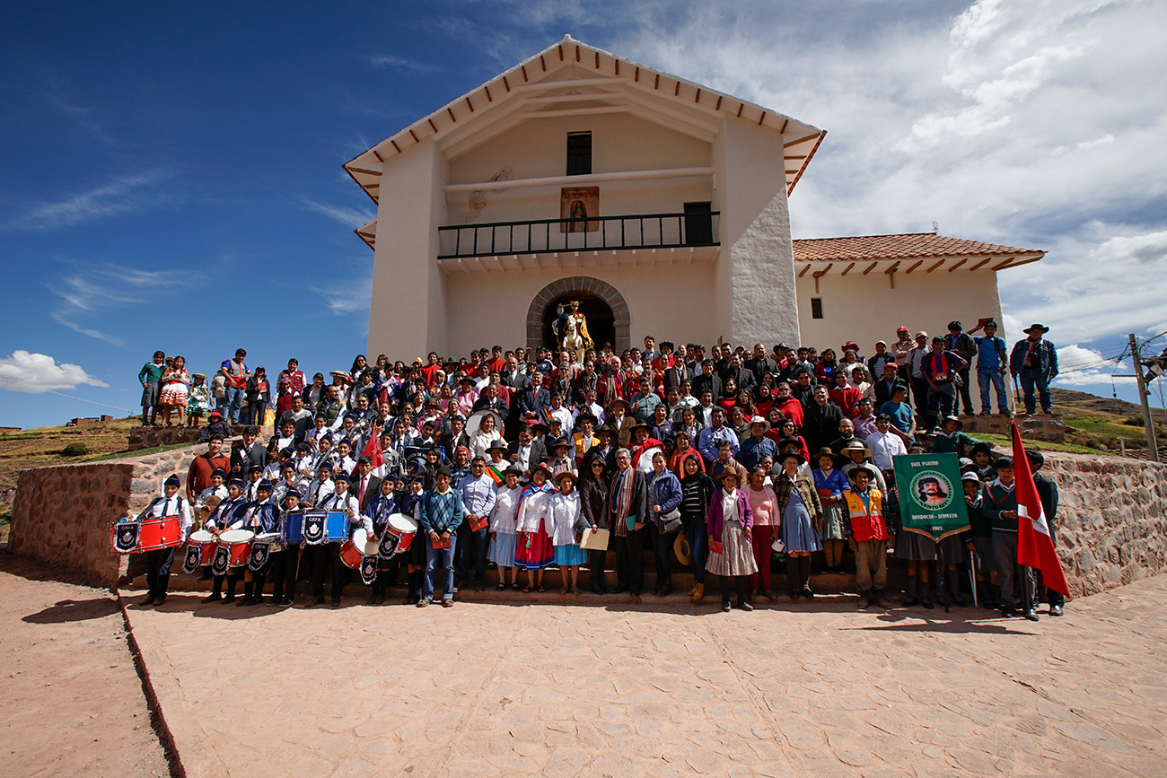 A large group stand for a photo in front of the Church of Kunotambo