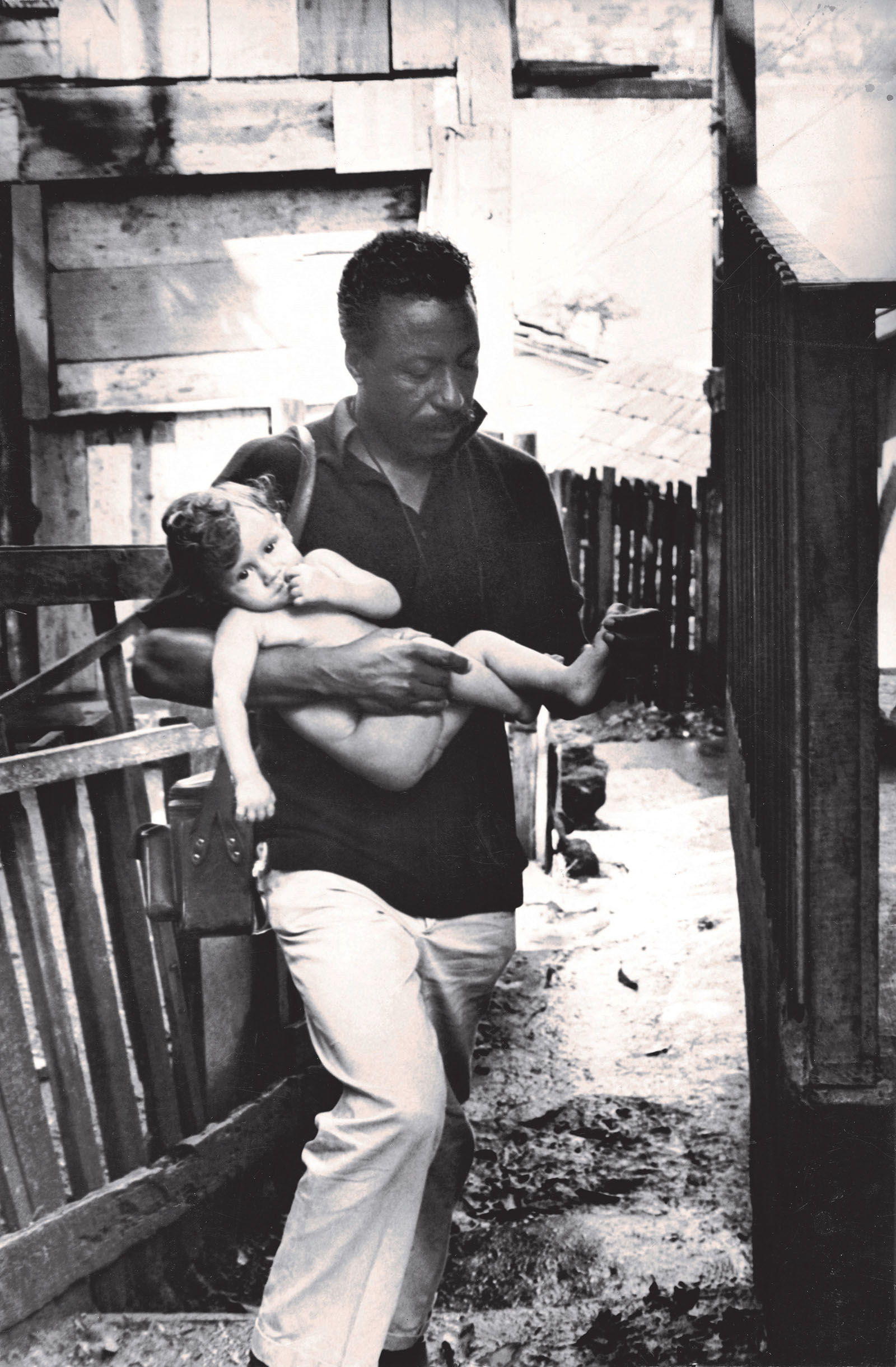 Gordon Parks in Brazil holding a baby.