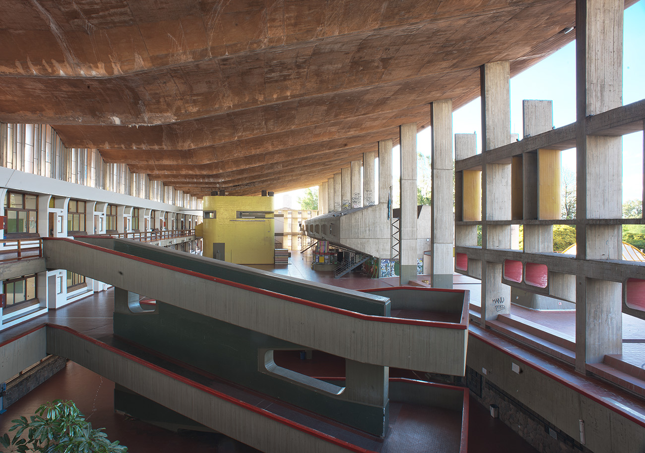 Inside but open-air cement building, with large open cement supports on the right, entrances to three stories of rooms on the left, and cement switchback ramps in the middle.