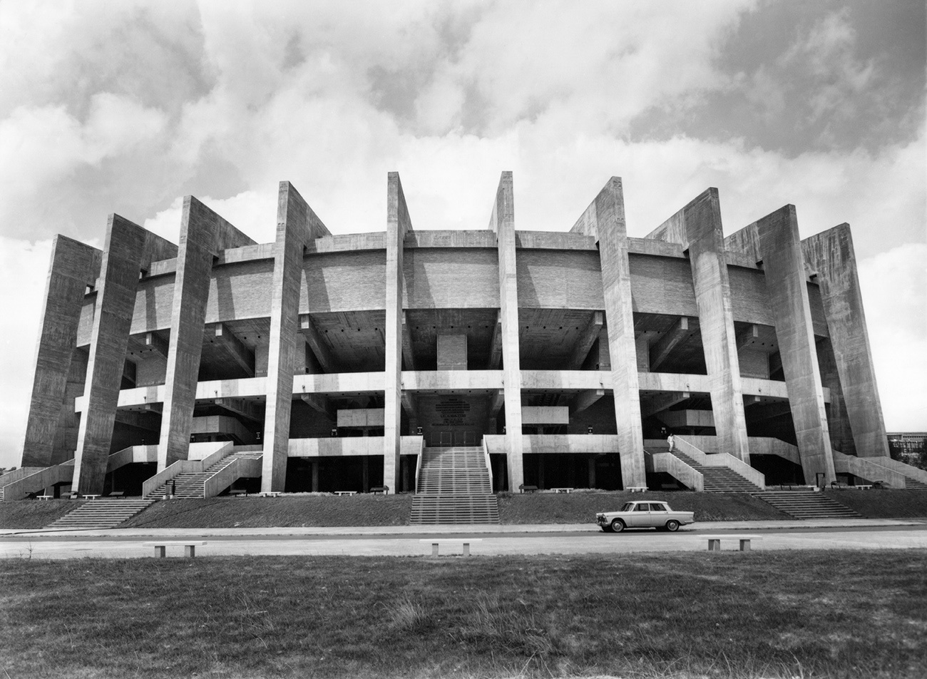 Black and white photo of a large concrete structure that looks like a giant, ten-legged spider. A boxy vintage car is parked in front.