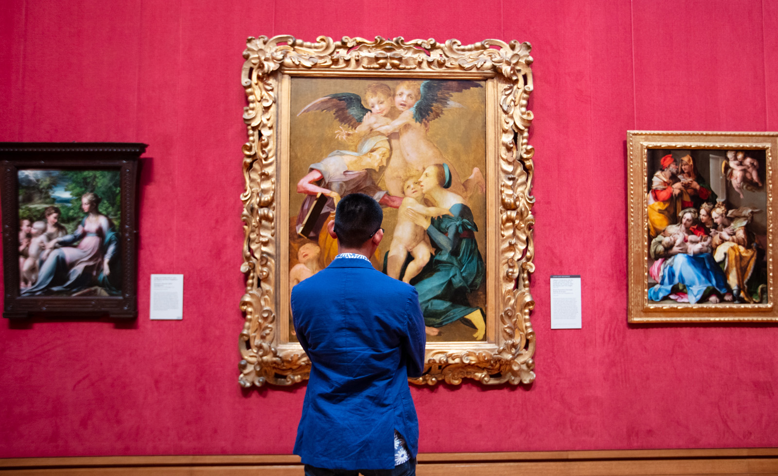 A man in a bright blue jacket looks at three paintings of the Holy Family.