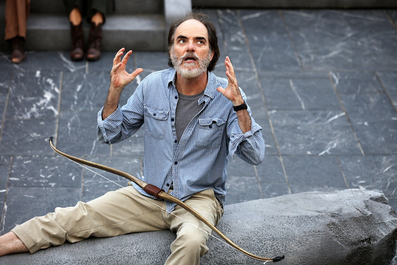 Close-up on a grizzled actor with his arms bent and fingers splayed, sitting on the ground and about to speak