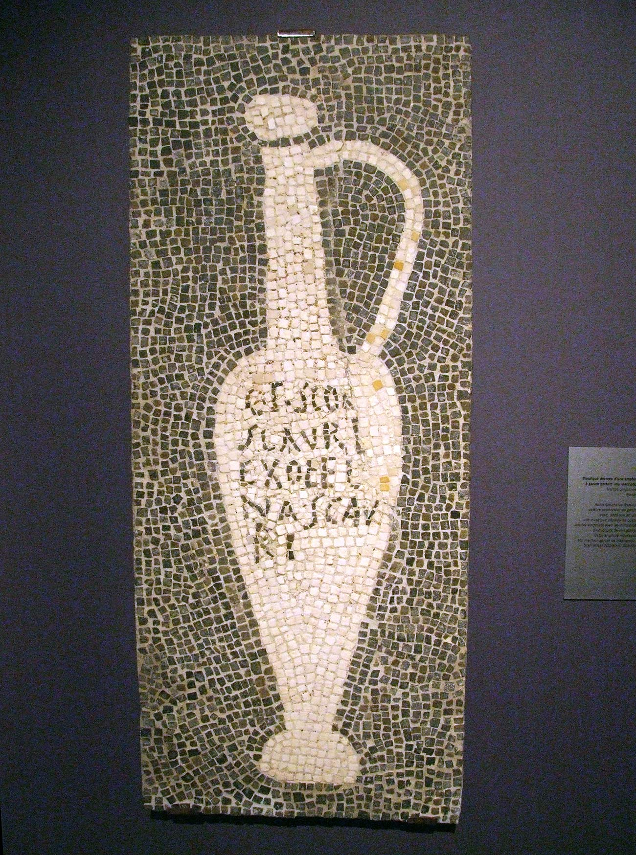 Mosaic hanging on a gallery wall showing a long, tall jar with a large handle and decorated with Latin lettering