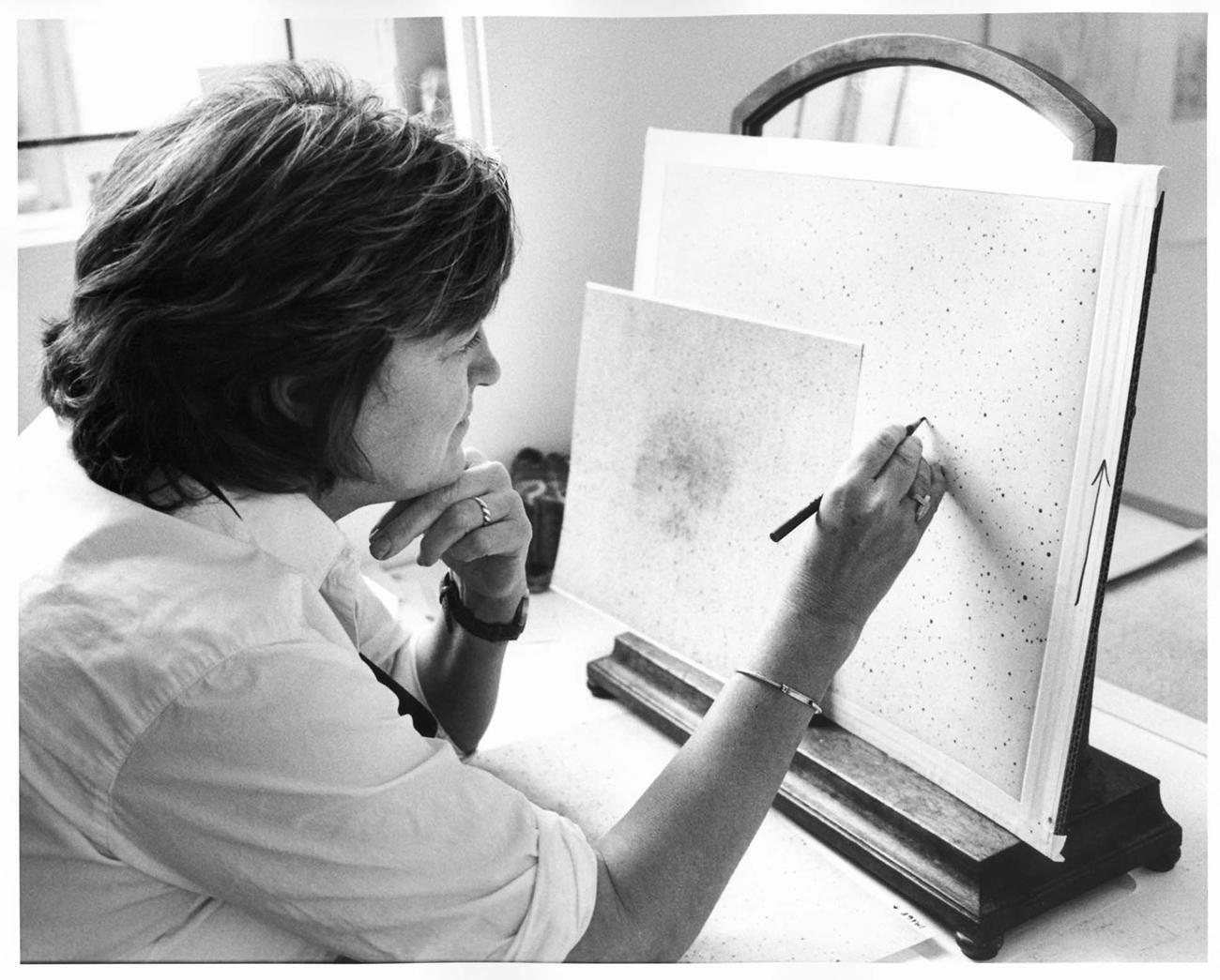 Artist Vija Celmins faces an easel and marks paper with a pencil