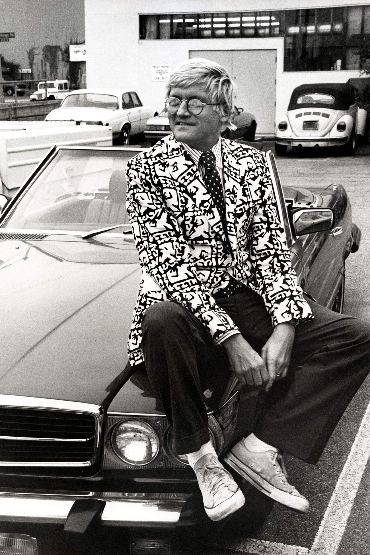 Artist David Hockney wears a patterned blazer and sits casually on the hood of a car, smiling.