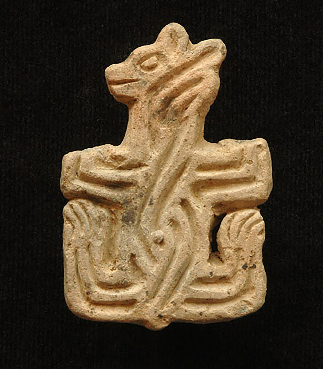 Ancient stone carving of a mammal with large paws and small ears, ornamented with sinuous lines