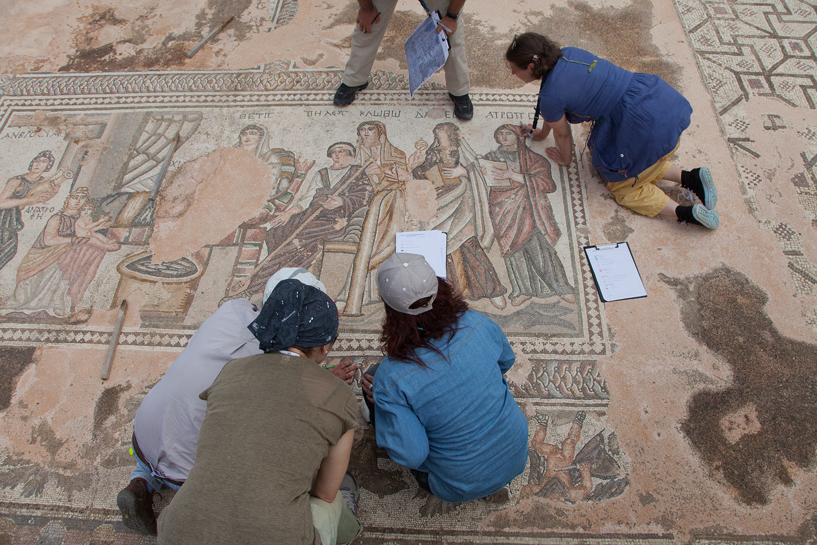 Overhead view of a small group of people down on their knees, closely assessing an ancient mosaic pavement