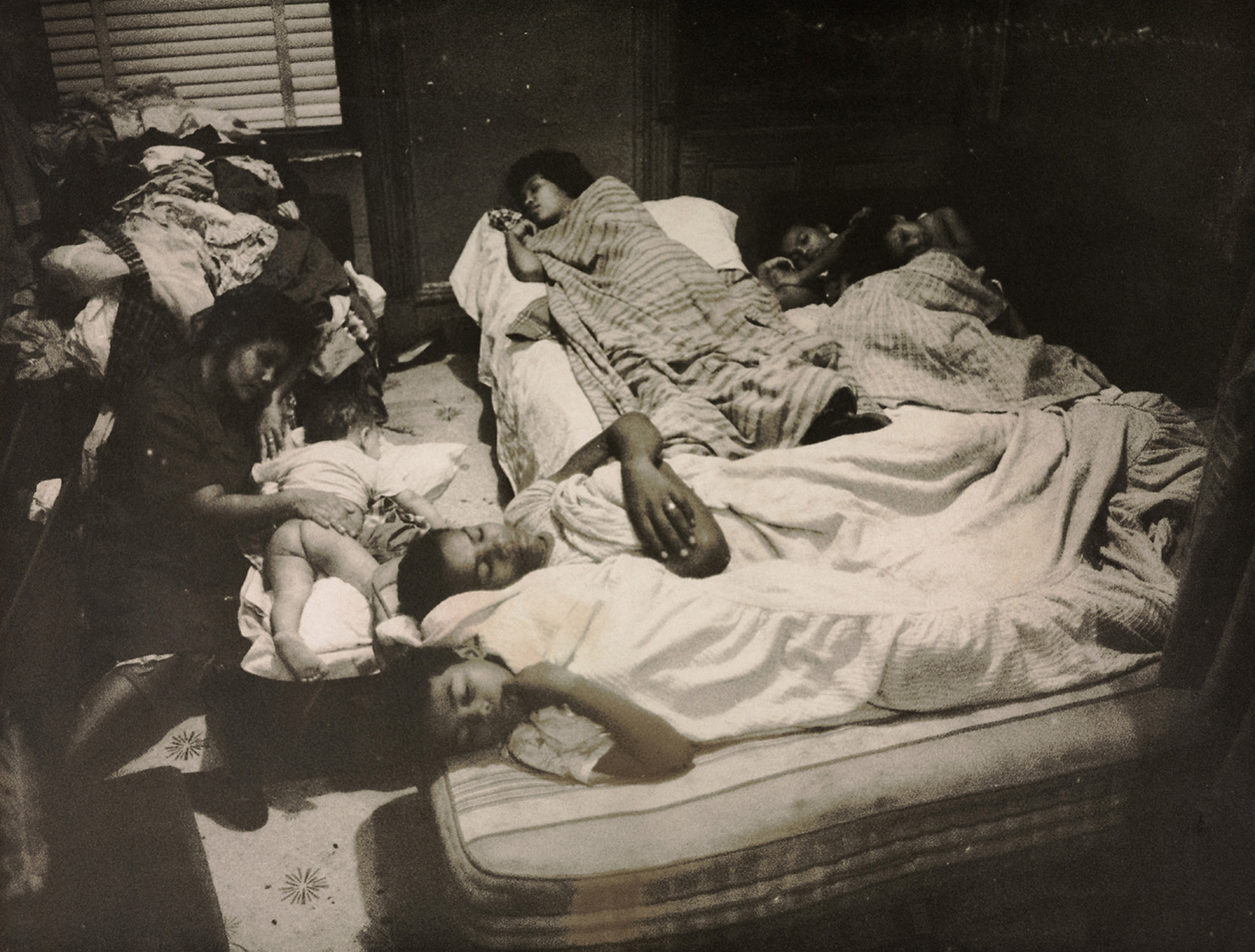 A family sleeping in a tiny room. They are crammed together on a mattress.