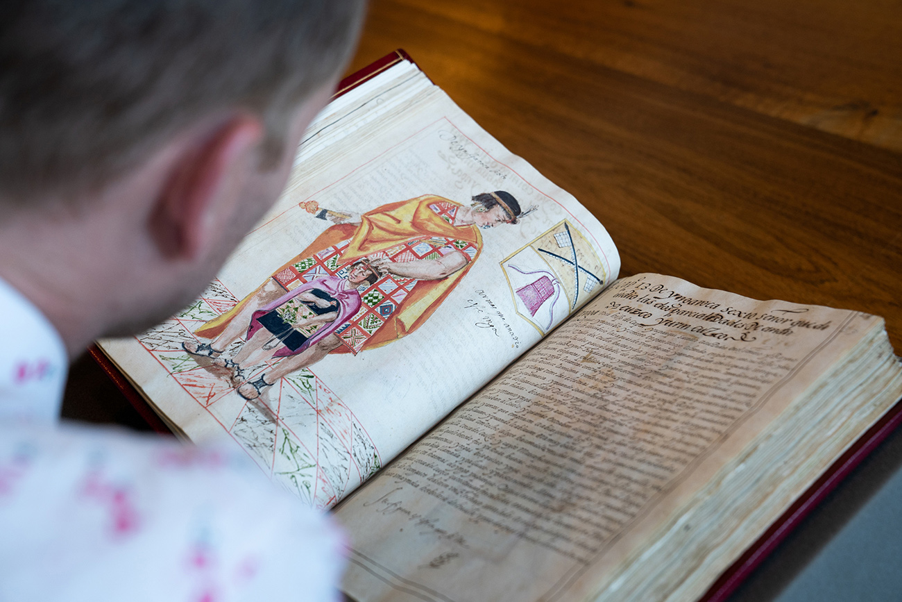Andrew looks at a page from an old book on which a male figure is depicted wearing a tunic patterned like the All-T'oqapu Tunic.