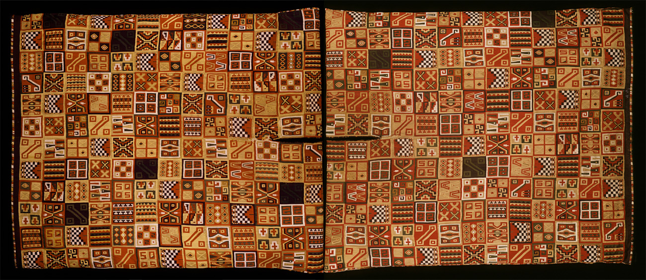 The long rectangular textile bears patterns in squares that are primarily red, black, white, and light brown.