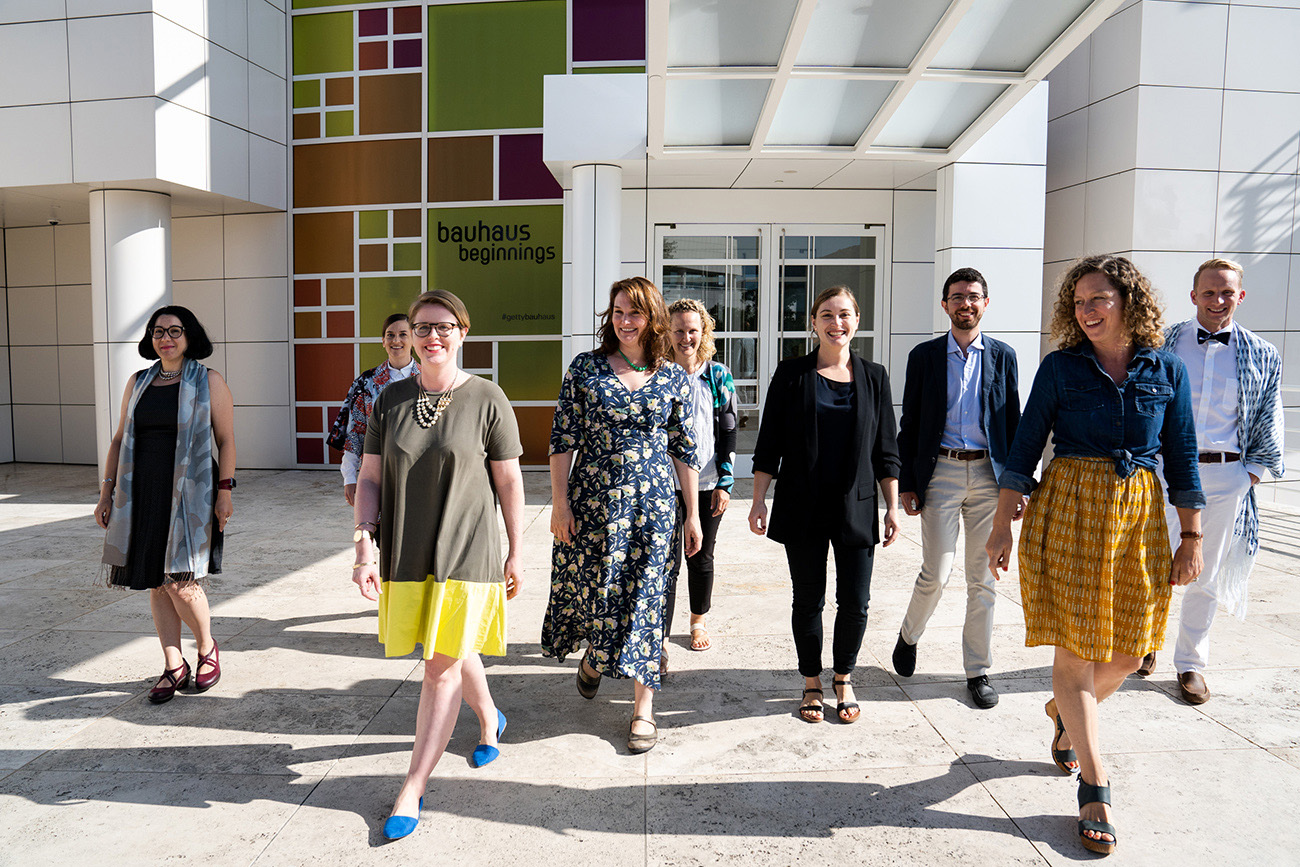 Outside the Getty Research Institute, nine people walk towards the camera.