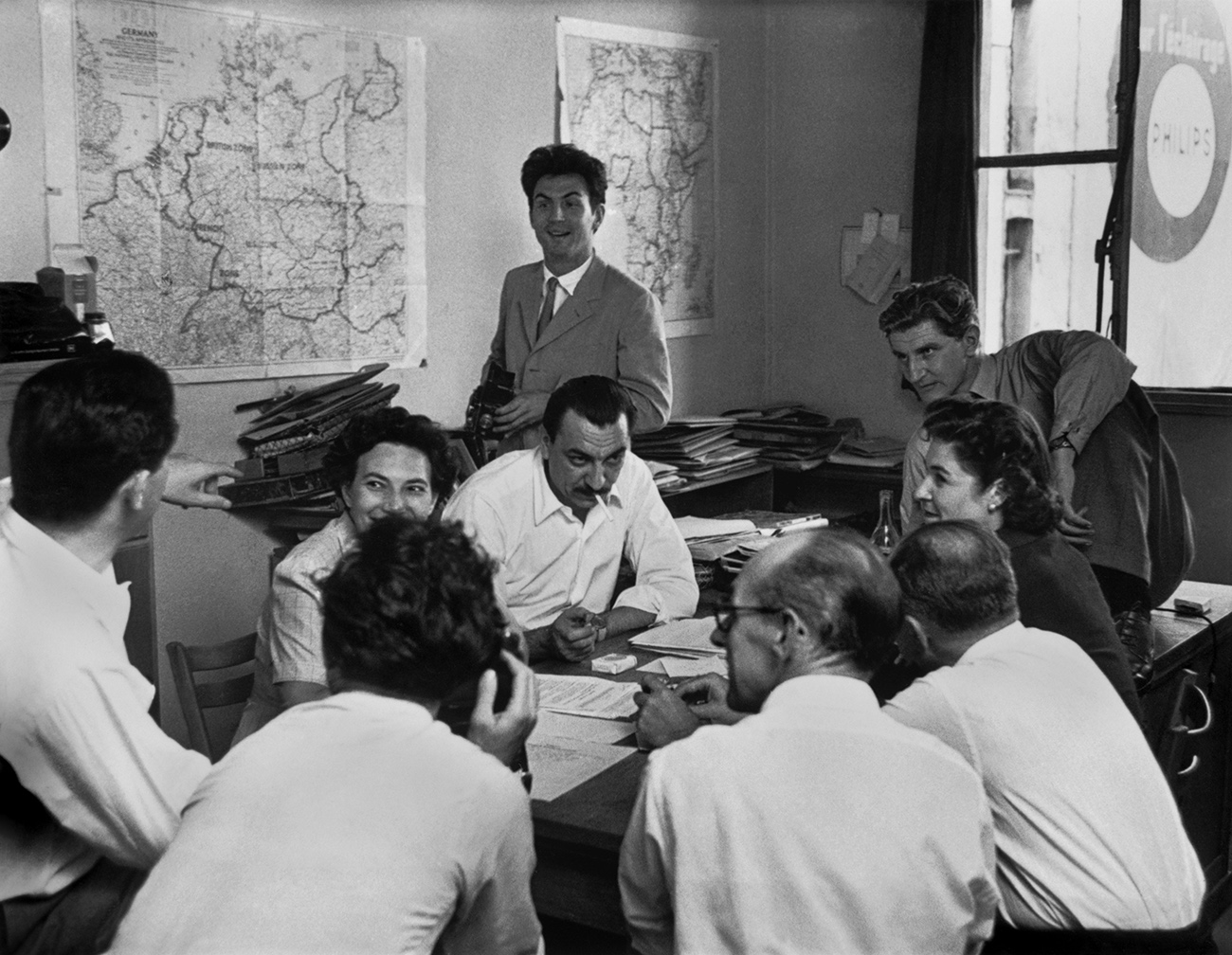 The black-and-white photograph shows several men and women in business attire in animated conversation.