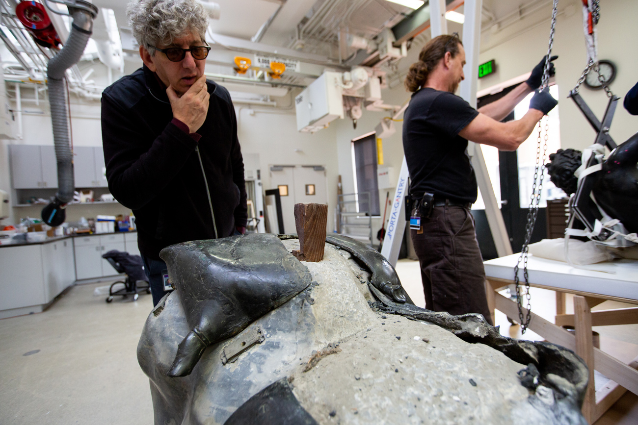 Curator Ken Lapatin inspects the base with the sculpture removed.