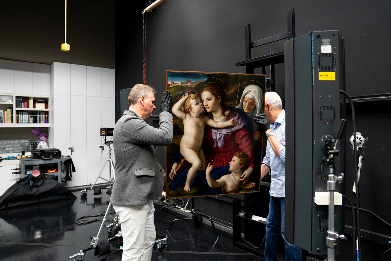 Two men wearing gloves position a Renaissance painting on an easel to be photographed