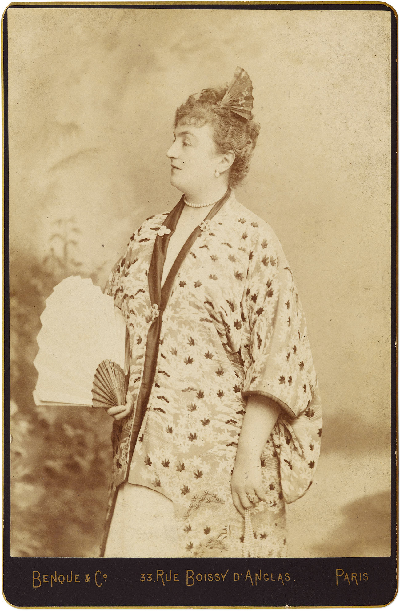 Sepia photo of a woman looking left, wearing a robe and holding a fan.