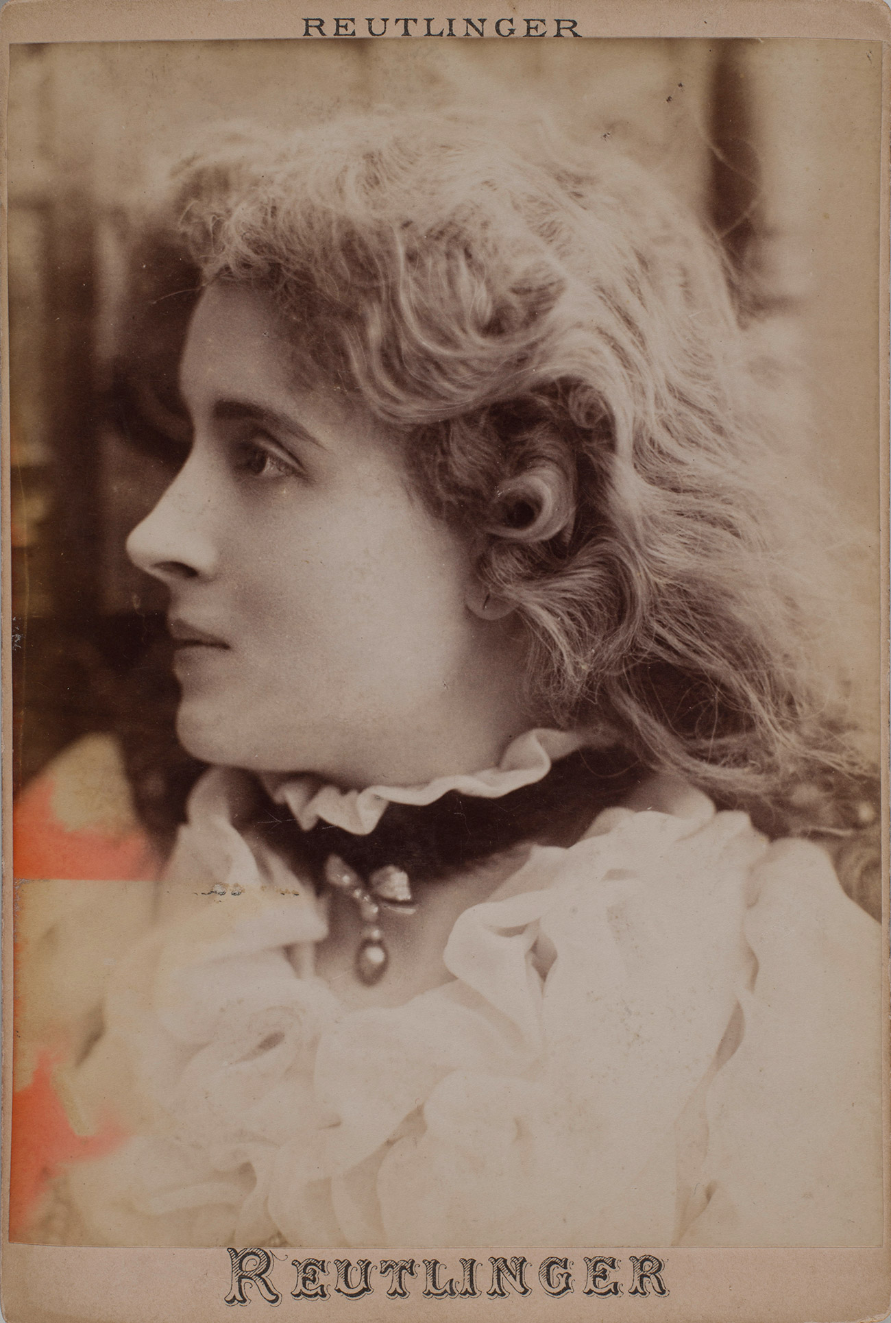 Sepia toned side portrait of a woman wearing white ruffles and a black neck band.