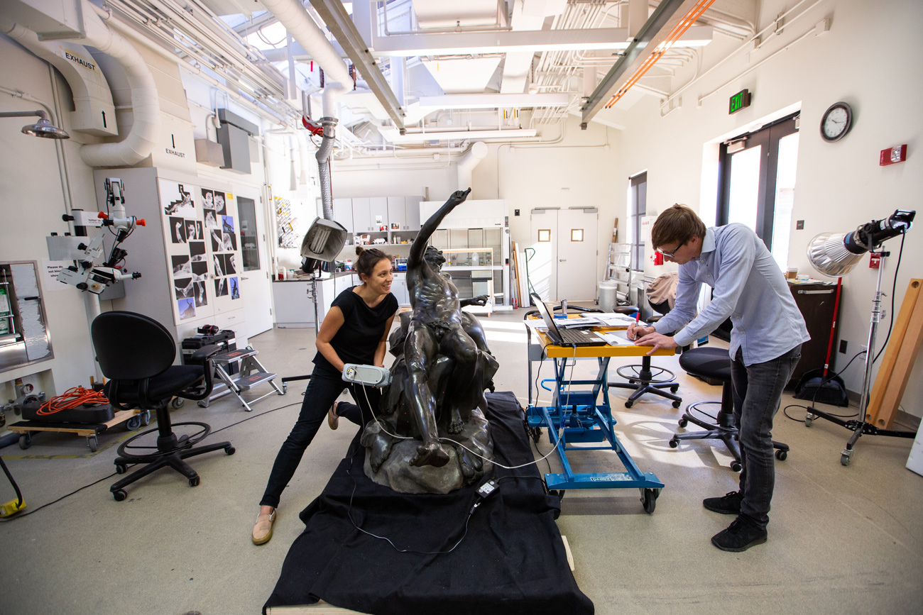 Monica squats near the satyr figure taking a sample with the xrf device as William sits nearby recording notes.