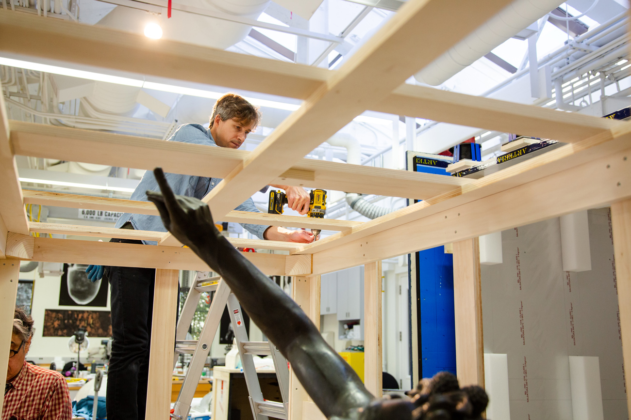 A preparator carefully removes screws from a wooden cage holding the ancient sculpture.