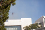 A fire helicopter flies north over the Getty Center Auditorium on Monday. Water and flame retardants dropped by air were critical to the fire response.