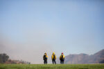 Firefighters stand at the perimeter of the Getty Center's helipad on Monday, coordinating response to flames at the Getty's northern edge.