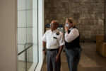 Two members of the Getty's security management stand in the Museum Entrance Hall on Monday, monitoring fire activity to the north of the Getty Center.