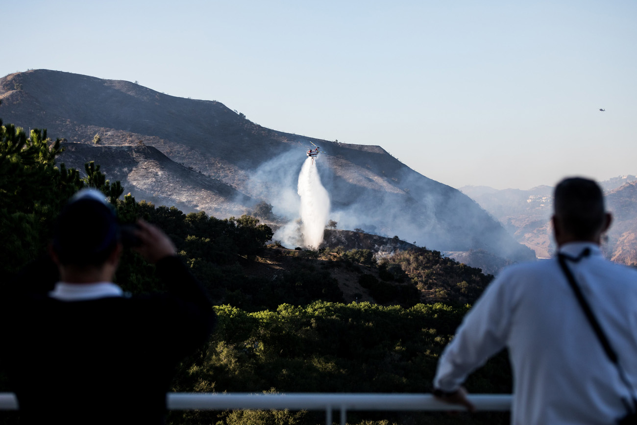 Two security officers watch as a helicopter dumps water onto a small fire flare up north of the Getty Center.