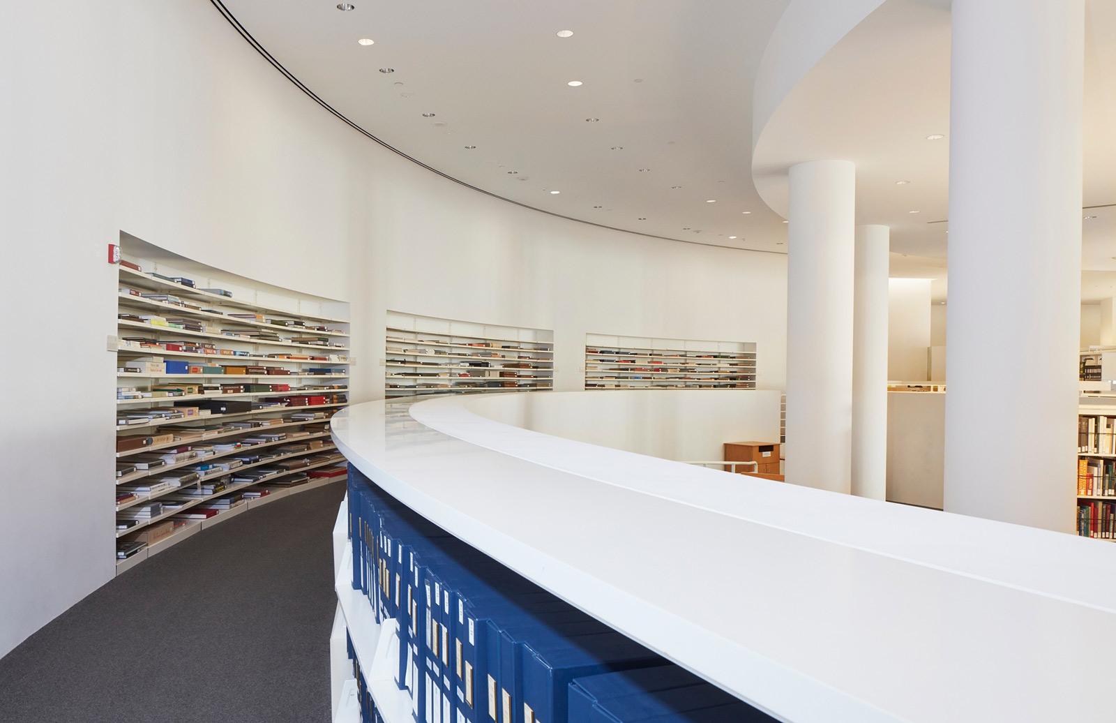 Photo inside the Getty Center library showing its curve white walls and shelves of horizontal books.