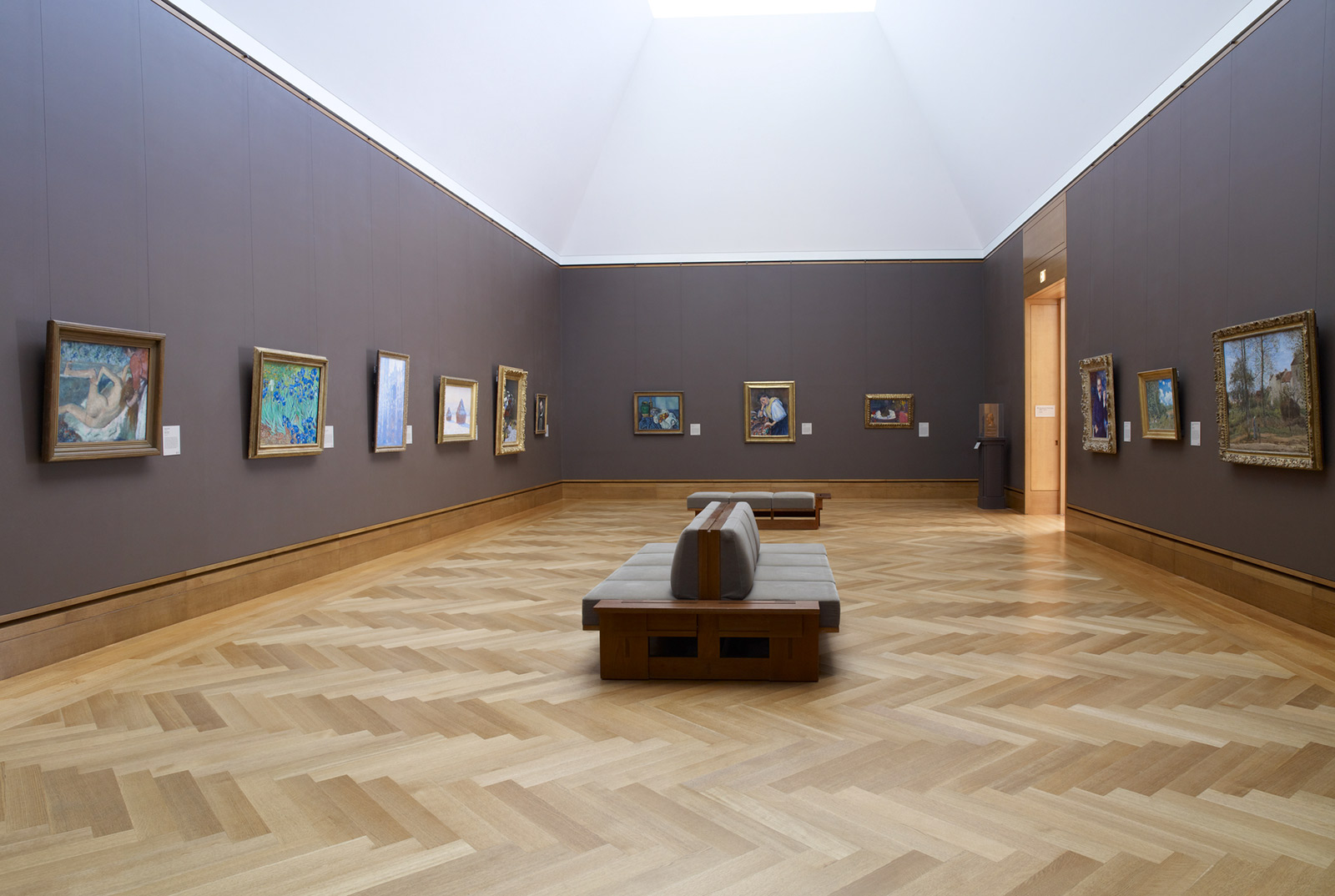 Wide-angle view of a museum gallery with mushroom-colored walls, a wood floor, and paintings in gold frames