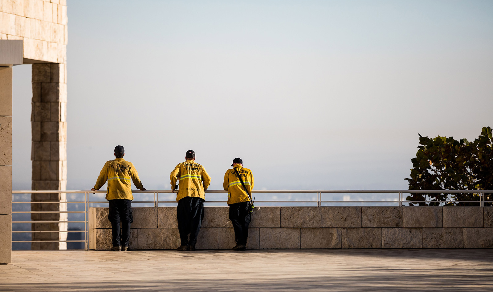 Three men in bright yellow firefighting jackets lean against a banister at the Getty Center, monitoring the landscape to the south