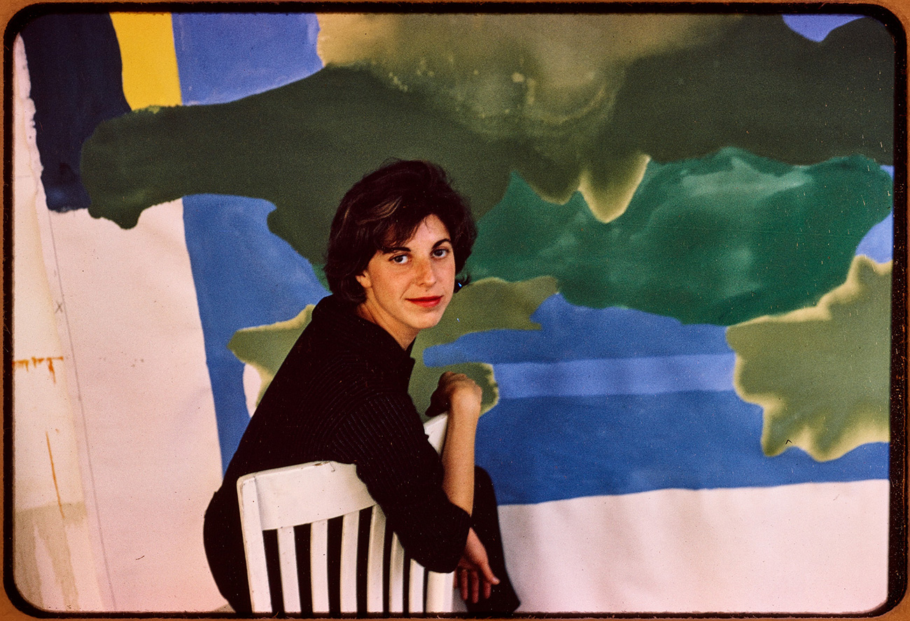 Helen sits and leans on the back of a white-backed chair, in front of an abstract painting of blues and greens.