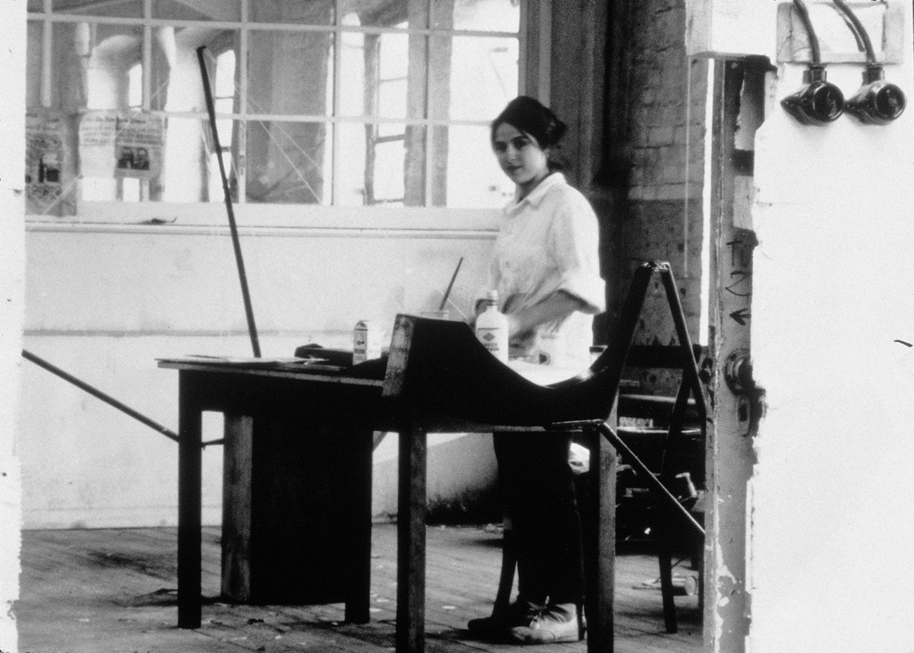 Eva wears a white shirt and dark pants, and stands before a drafting table. There are mirrored windows behind her to the left, and a brick wall behind her to the right.
