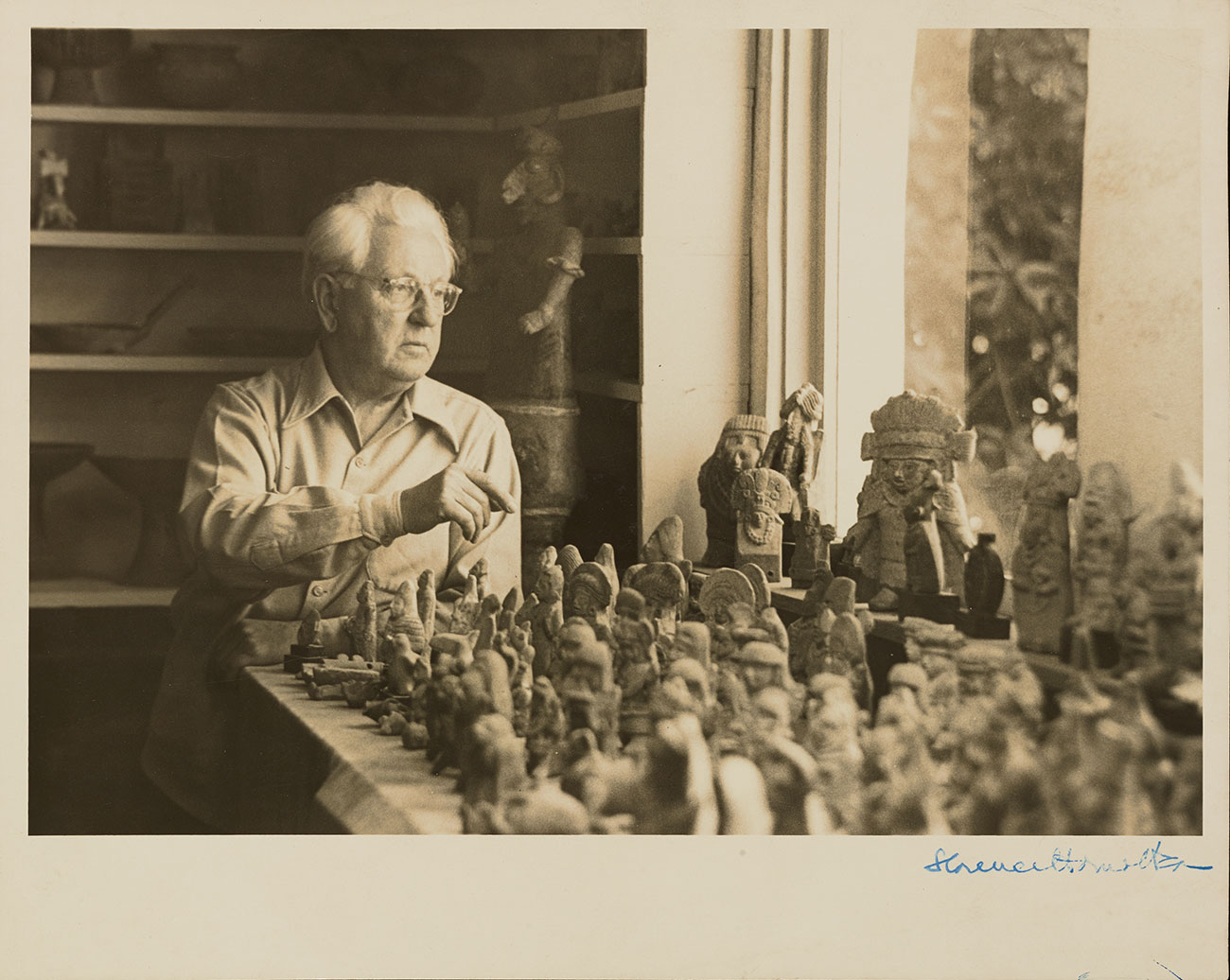 Sepia-toned black and white photo showing a seated man with white hair behind a table filled with small pre-Hispanic ceramic figurines