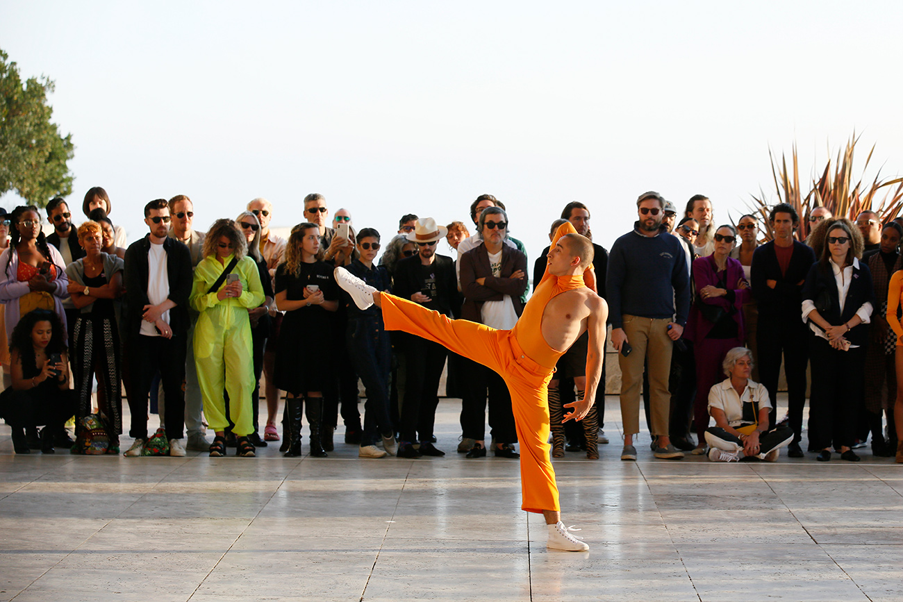 A single dancer dressed in orange, standing on one leg with the other leg raised high, while a crowd watches from behind.