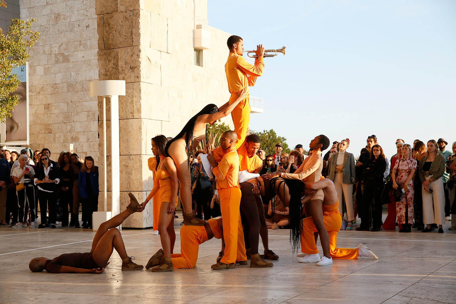 Dancers dressed in orange and brown form a small pyramid, supporting a trumpet player at the top, while a crowd looks on from the back.
