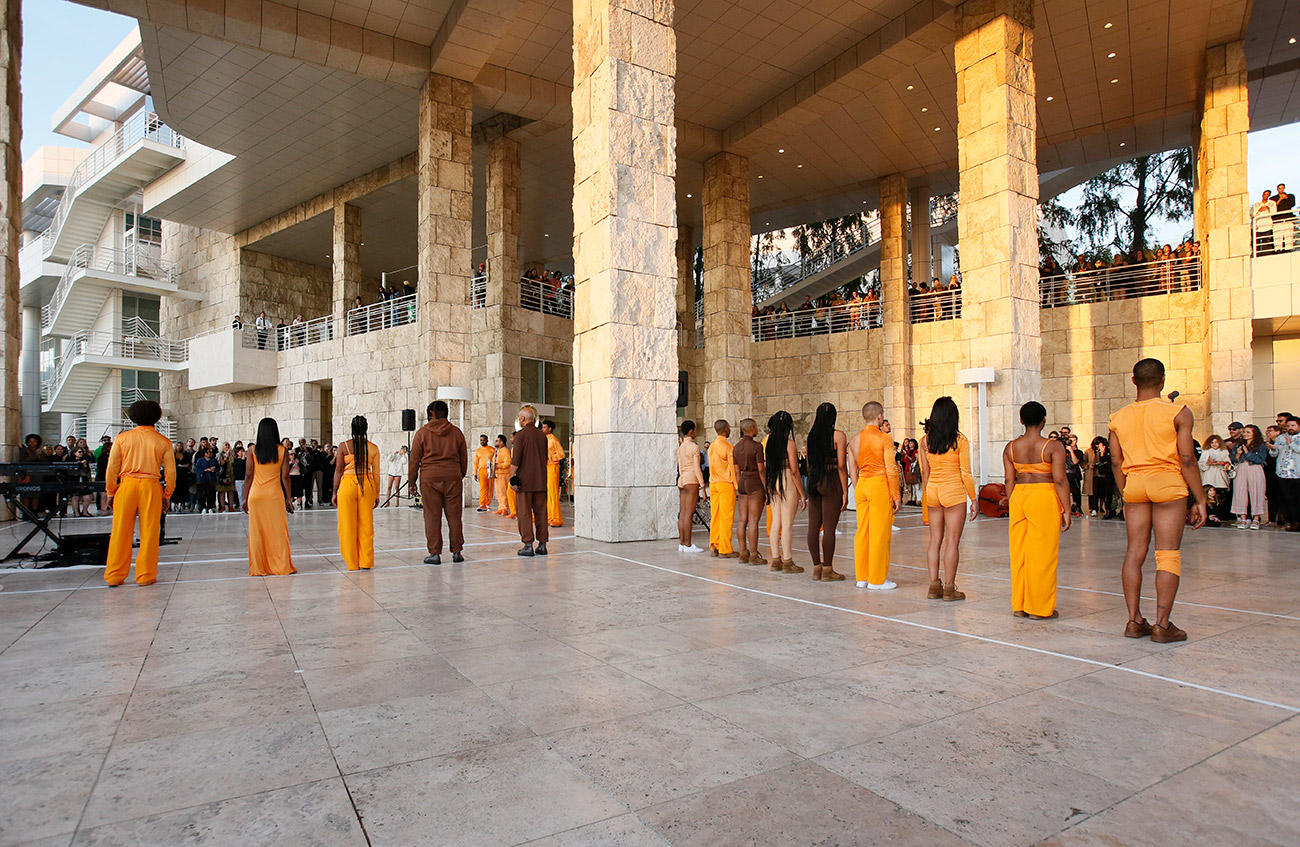Dancers dressed in orange stand in two perpendicular lines, surrounded by travertine columns.
